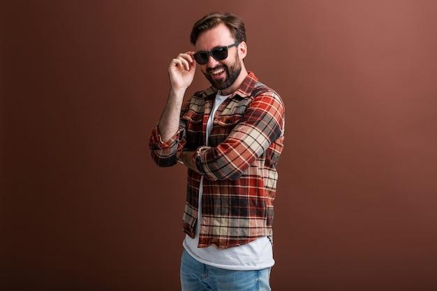 Brutale hipster mannelijke knappe stijlvolle bebaarde man op bruin