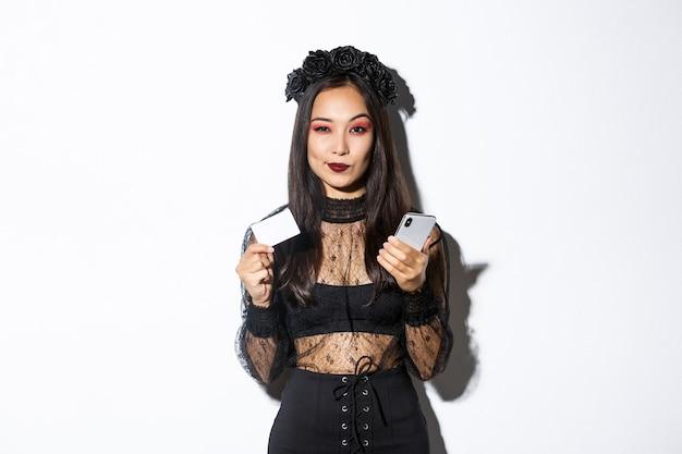 Brutale jonge vrouw die nadenkend kijkt, creditcard en mobiele telefoon vasthoudt, winkelt op internet, staande op een witte achtergrond.