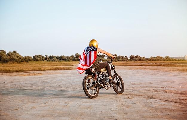 Brutale jongeman in gouden helm en amerikaanse vlagkaap retro motorfiets rijden