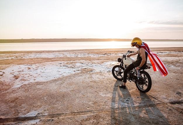Brutale jongeman in gouden helm en amerikaanse vlagkaap zittend op zijn motorfiets
