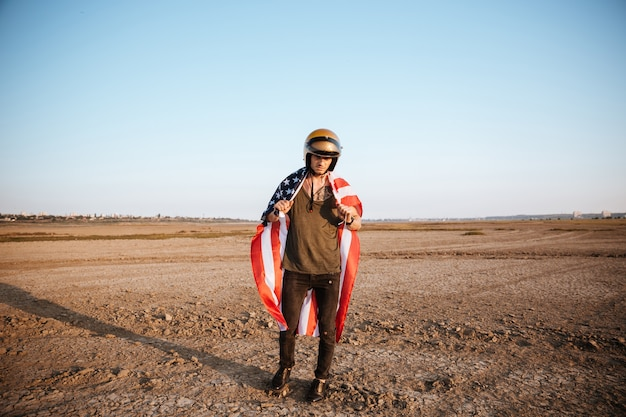 Brutale jongeman met amerikaanse vlagkaap en gouden helm poseren in de woestijn