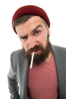 Brutale kaukasische hipster met snor. rijpe hipster met baard. bebaarde man. slechte gewoonten en verslaving. man roken sigaret. serieuze man met opgetrokken wenkbrauw. mannelijke kapper zorg. haar- en baardverzorging.