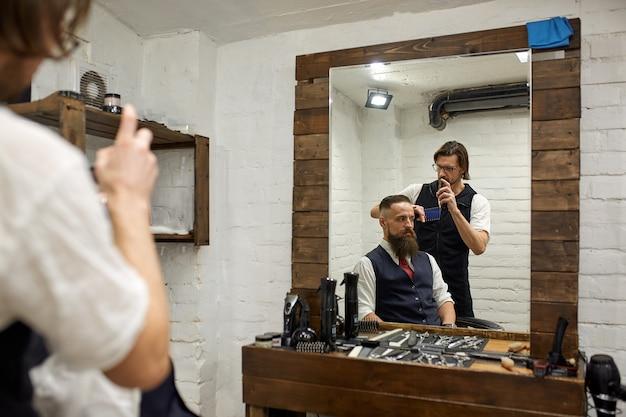 Brutale kerel in moderne kapperszaak. kapper maakt kapsel een man met een lange baard. hoofdkapper doet kapsel met een schaar en kam