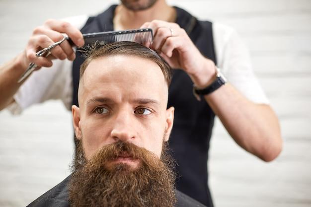Brutale kerel in moderne kapperszaak. kapper maakt kapsel een man met een lange baard. hoofdkapper doet kapsel met haartrimmer