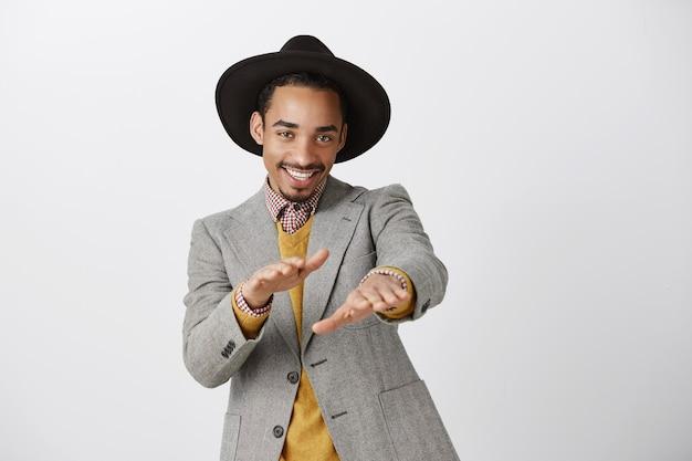 Brutale knappe afro-amerikaanse man in pak dansen en gelukkig glimlachen