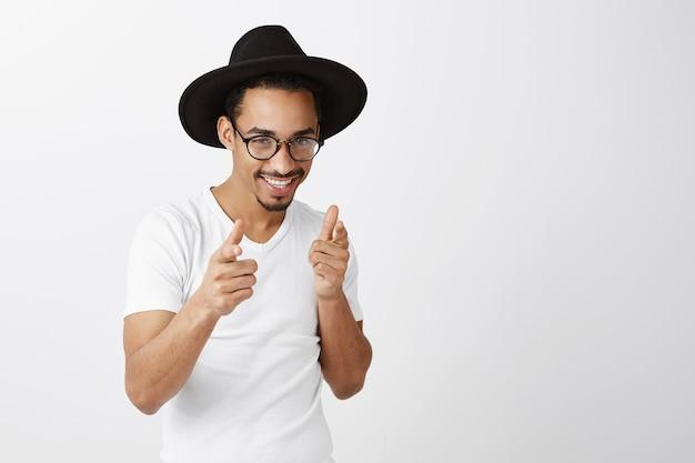 Brutale knappe afro-amerikaanse man in stijlvolle outfit wijzende vingers, gefeliciteerd, goed gedaan gebaar