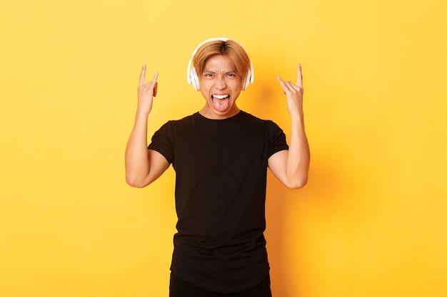 Brutale knappe aziatische man houdt van heavy metal, luistert naar harde rockmuziek, toont rock-n-roll-gebaar en draagt een draadloze koptelefoon, steekt tong, staande gele muur