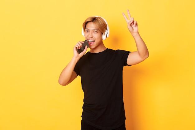 Brutale knappe aziatische man in koptelefoon, karaoke-app spelen, zingen in de microfoon van de mobiele telefoon, vredesgebaar tonen, gele muur staan