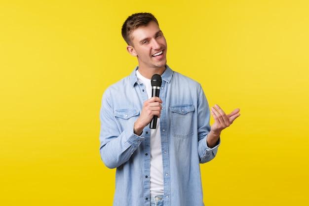 Brutale knappe blonde man in vrijetijdskleding voert toespraak, stand-up show voor publiek, zingt lied en lacht brutaal, staande gele achtergrond, genietend van karaoke-avond, microfoon vasthoudend.