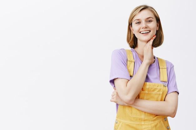 Brutale knappe jonge vrouwelijke student lachend, gezicht aanraken met een tevreden blik
