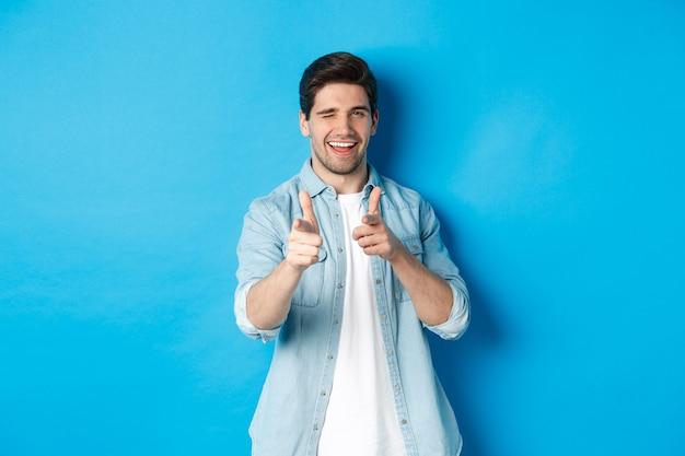 Brutale knappe kerel die met de vingers naar je wijst, flirterig knipoogt, in een casual outfit tegen een blauwe achtergrond staat