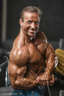 Brutale leeftijd sterke bodybuilder atletische mannen oppompen van spieren met halters