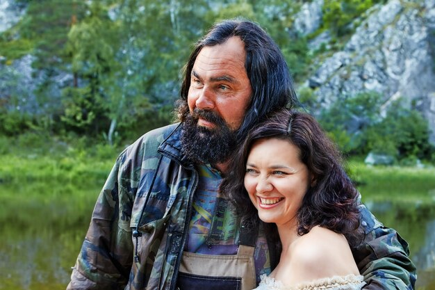 Brutale man knuffelt vrij volwassen vrouw die lacht.