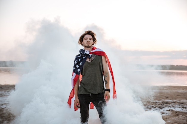 Brutale man met usa vlag cape poseren in witte rook buitenshuis