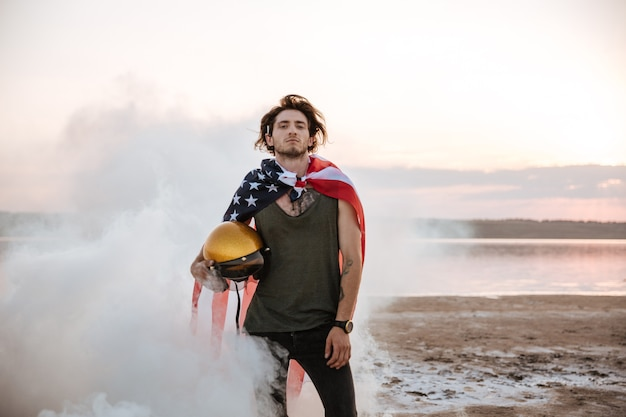Brutale man met usa vlag cape poseren in witte rook en gouden helm buitenshuis te houden