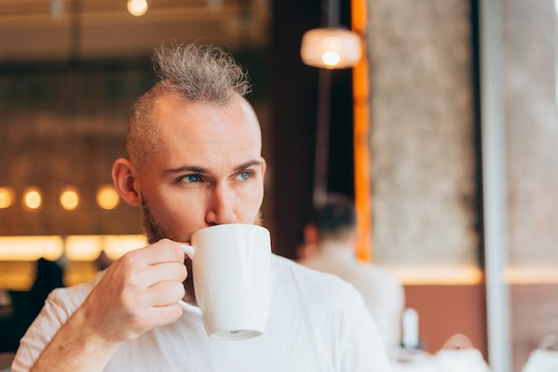 Brutale man van europese uitstraling in een café in de ochtend met een kop warme koffie