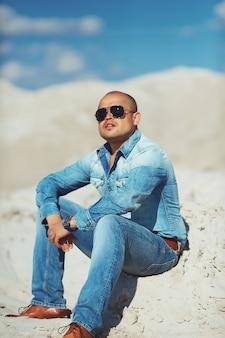 Brutale man zittend op het zand, gebronsd