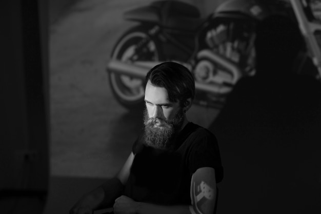 Brutale mannelijke fietser die door de dia's van zijn motorfiets kijkt. het concept van levensstijl