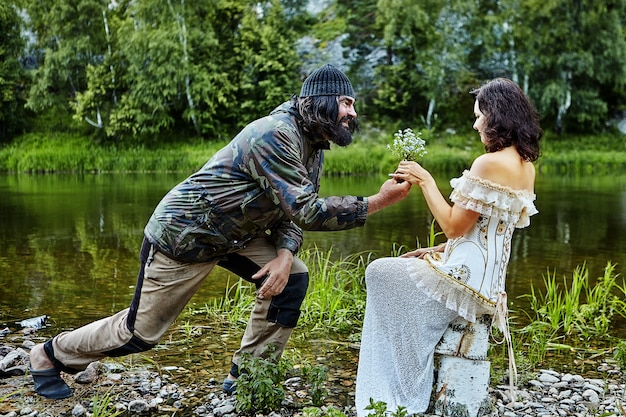 Brutale ruige man, gekleed in kampeerkleding, geeft een boeket wilde bloemen aan een vrouw in een avondjurk, te midden van de natuur met rivier en bos.