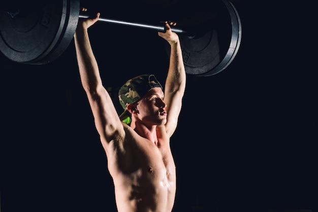 Brutale spiermens met baardtrein met barbell opgeheven lucht in gymnastiek