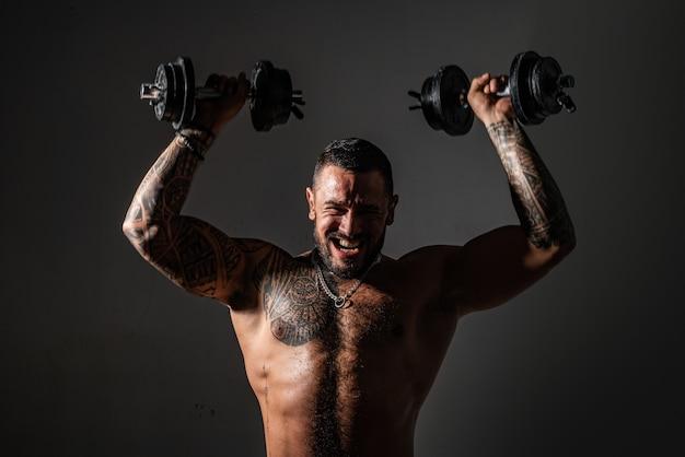 Brutale sportman met barbell. steroïden. vertrouwen charisma. sexy buikspieren van tattoo man. mannelijke mode. gespierde macho man met atletisch lichaam. sporten en fitnessen. dumbells tillen. trainen met coach