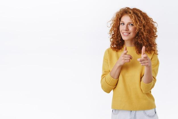 Brutale, vriendelijke knappe roodharige krullende vrouw in gele trui, wijzende vingerpistolen naar de camera en glimlachen, je plukken, speels groeten of feliciteren met de persoon, witte muur