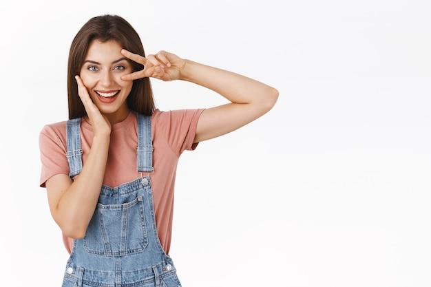 Brutale, vrolijke jonge vrouw in overall, t-shirt, vredesteken of overwinningsteken boven oog in discobeweging, wang zachtjes aanraken, vastberaden en zelfverzekerd kijken, zelfverzekerd op een witte achtergrond staan