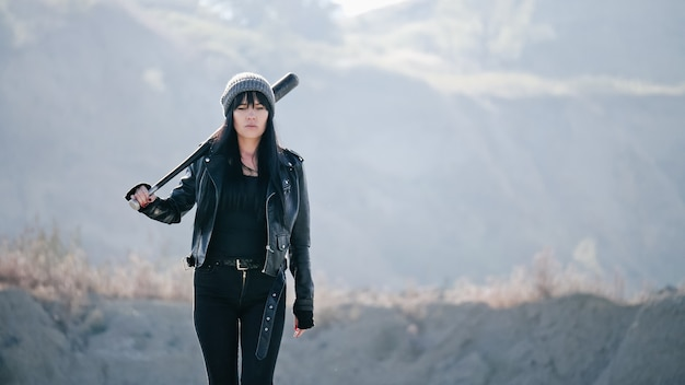 Brutale vrouw van hooligan-bendes gaat met een honkbalknuppel in de woestenij.
