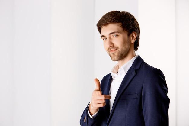 Brutale zelfverzekerde knappe jonge zakenman, wijzende vinger en lachend, prees je goed werk te maken