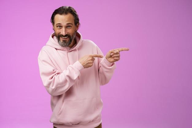 Brutale zelfverzekerde knappe macho-man 50s in roze hoodie glimlachend breed uitnodigend sluit je aan en wijst naar rechts met een interessante, grappige plek, rondhangen, verwelkomend kijken, staande op een paarse achtergrond.