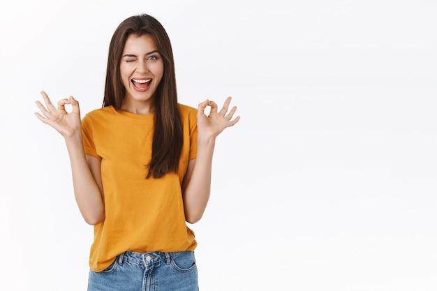 Brutale, zorgeloze knappe jonge brunette vrouw die niets zegt over zorgen, oke, ok of goedkeuringsbord tonen, knipogen als hint geven en opgewonden glimlachen, staande witte achtergrond