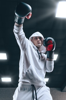 Brute atleet boksen in de ring in een witte hoodie bedekt met een capuchon. gemengd vechtsportenconcept.