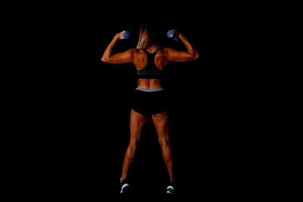 Brute atletische vrouw die spieren oppompt met halters sexy aantrekkelijke fitness vrouw