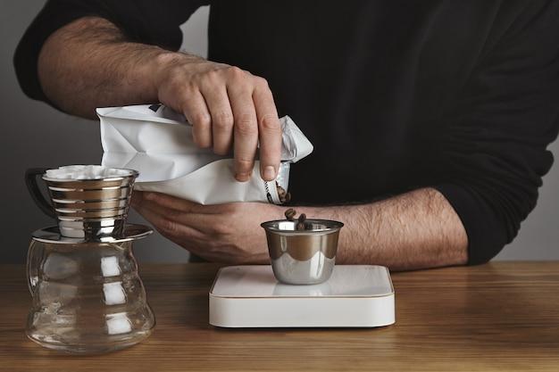 Brute barista in zwarte sweatshot giet gebrande koffiebonen in roestvrijstalen beker. chromen infuus koffiezetapparaat in de buurt van cafe winkel
