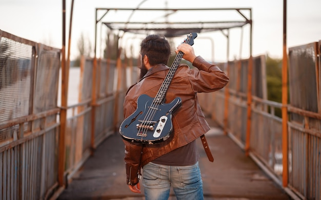 Brute bebaarde fietser met grijze haren in een bruin leren jas en spijkerbroek staat met zijn rug en houdt een zwarte elektrische gitaar op zijn schouder