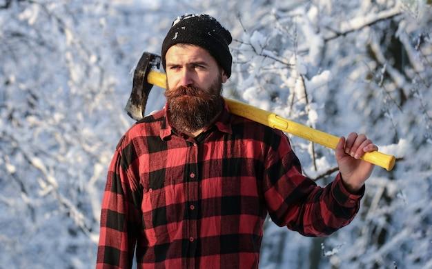 Brute bebaarde houthakker met bijl in winter woud. houthakker met een bijl in zijn handen. mannetje houdt een bijl op een schouder. brutale bebaarde man. knappe man, hipster in besneeuwde bossen.