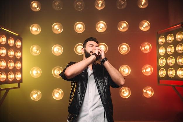 Brute bebaarde zangeres met microfoon op het podium