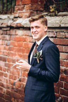 Brute bruidegom in een pak en stropdas rookt een sigaret.