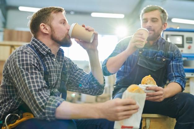 Brute collega's die koffie in fabriekswinkel drinken
