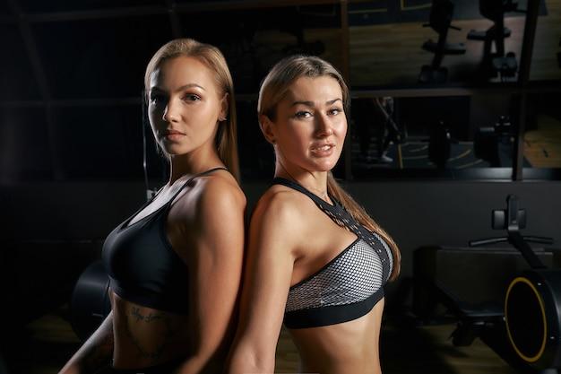 Brute fitness twee vriendinnen met een gespierde in de sportschool. sport en fitness - concept van een gezonde levensstijl. fitness vrouw in de sportschool.