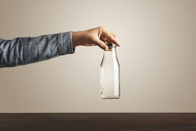 Brute hand in jeans jasje houdt glazen transparante fles met schoon drinkwater voor zwarte metalen dop boven rode houten tafel, geïsoleerd op wit