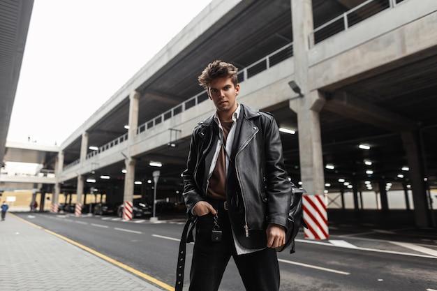 Brute jonge hipster man in trendy zwarte vrijetijdskleding poseren in de stad in de buurt van de weg. stijlvol modern stadsmodel in een vintage leren jas oversized in broek buitenshuis. amerikaanse straatmode