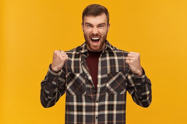 Brute kerel met baard, opgewonden uitziende man met donkerbruin haar. een geruit overhemd en accessoires dragen. balken zijn vuisten en vier de overwinning. geïsoleerd over gele muur