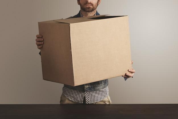 Brute koerier met baard in spijkerbroek werkjas houdt grote kartonnen kartonnen doos met goederen boven houten tafel.