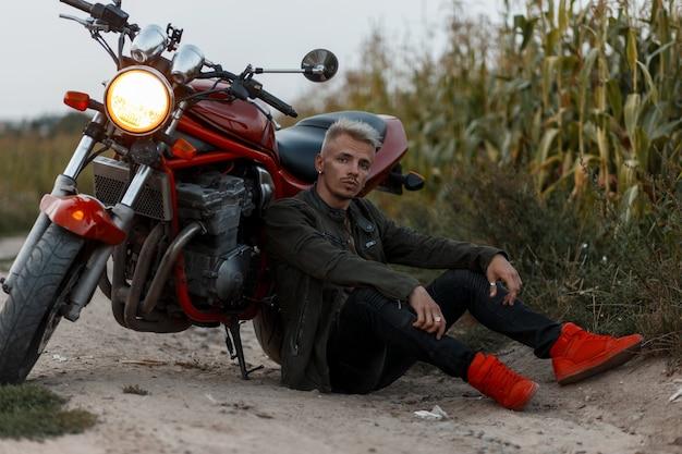 Brute model man in een militaire kaki jas van mode met rode stijlvolle sneakers zit in de buurt van een motorfiets in een korenveld