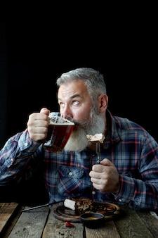 Brute volwassen man met grijs haar, gek op mosterdsteak en bier, vakantie, festival, oktoberfest of st. patrick's day