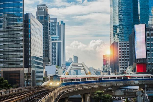 Bts skytrain, elektrische trein, onderweg met zakelijke kantoorgebouwen op de achtergrond.