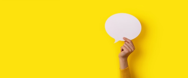 Bubble toespraak lay-out in de hand over gele achtergrond, panoramische mockup