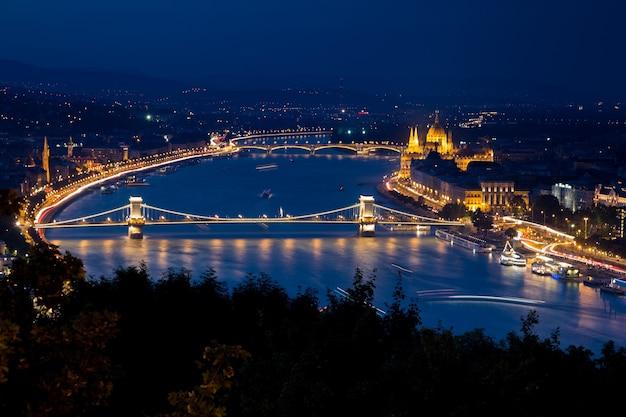 Buda castle omgeven door gebouwen en lichten tijdens de nacht in boedapest