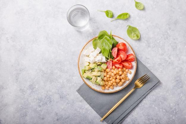 Buddha bowl met avocado, kikkererwten, feta-kaas, verse spinazie, tomaten en een glas water.